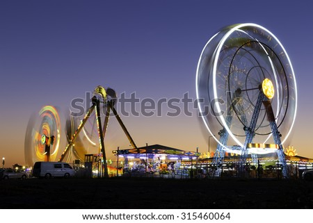 Colorful carnival Ferris wheel and gondola spinning in motion blurred at twilight in an amusement park - stock photo