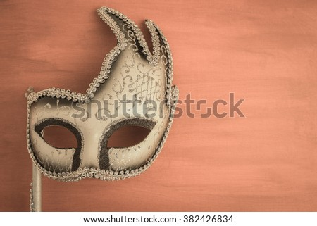 Colorful carnival mask on a brown textured background. Masks with theater concept. Top view with copy space - stock photo
