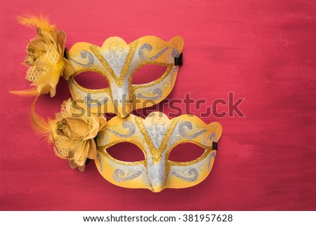 Colorful carnival mask on a red textured background. Masks with theater concept. Top view with copy space - stock photo