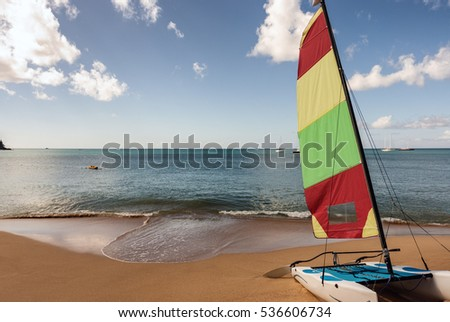 Colorful catamaran sail boat rests on tropical beach