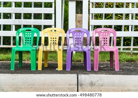 Colorful chairs in front of house and garden.