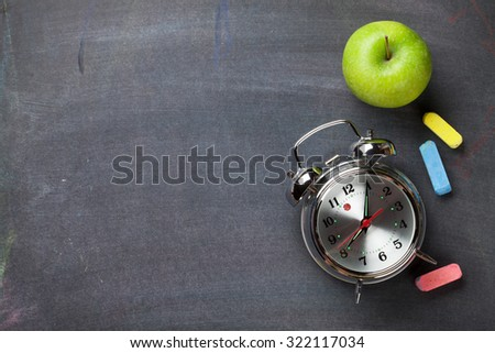 Colorful chalk, alarm clock and apple on blackboard background. Top view with copy space - stock photo