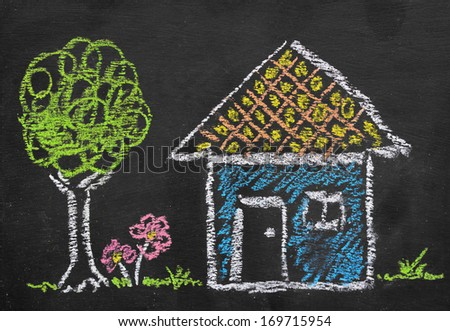 Colorful chalk illustration of home by kid on blackboard  - stock photo