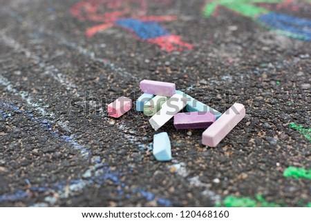 Colorful chalks on asphalt, child drawing - stock photo