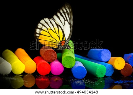 Colorful chalks on black background with butterfly