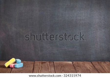 Colorful chalks on classroom table in front of blackboard. View with copy space - stock photo