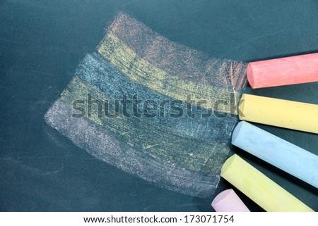 Colorful chalks on school desk - stock photo
