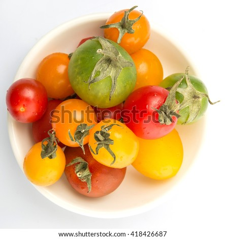 Colorful cherry tomatoes in white bowl over white background
