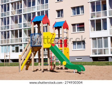 Colorful children playground in nature, front of row newly built block flats - stock photo