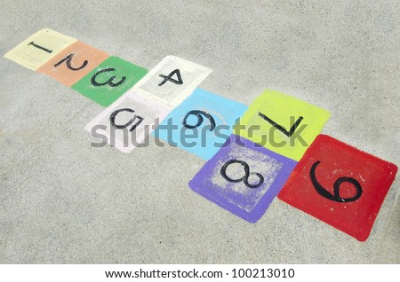 Colorful children's hopscotch on playground concrete. Concept photo of child, childhood, young, outdoor, game , memory, nostalgia, kindergarten, past,sentimentality.  - stock photo