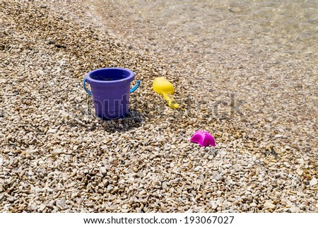 Colorful children's toys scattered on the sand at the beach in sunny day