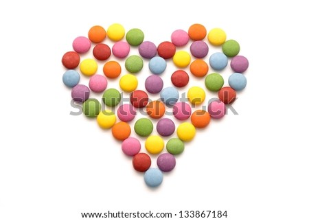colorful chocolate candy in the shape of heart on white background - stock photo