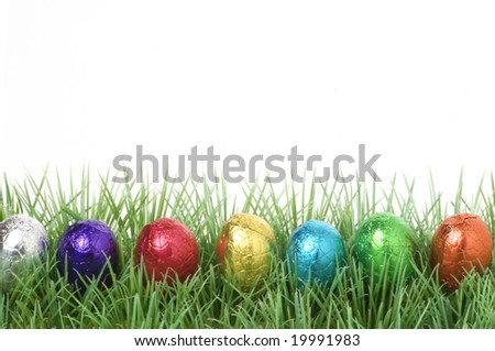 colorful chocolate easter eggs in a row on grass with copy space