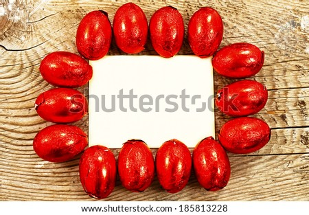 Colorful chocolate Easter eggs wrapped in foil on wooden background