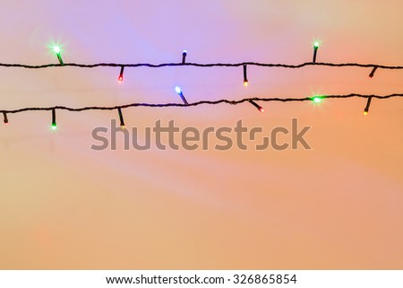 Colorful Christmas lights stream background - A bright multicolor festive background created by a stream of wired Christmas lights against a wall.
