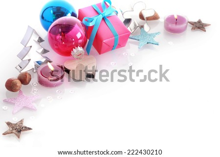 Colorful Christmas still life with blue and red baubles, gift , burning candles, stars, nuts and a Christmas tree shaped cookie cutter over white with copyspace for your Xmas greeting - stock photo