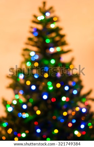 Colorful Christmas tree lights bokeh - A bright multicolor bokeh created by a set of de-focused lights on a Christmas tree. - stock photo