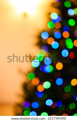 Colorful Christmas tree lights bokeh - A bright multicolor bokeh created by a set of de-focused lights on one half of a Christmas tree. - stock photo