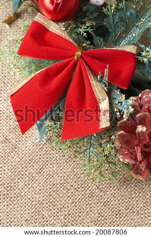Colorful Christmas wreath with red bow, balls and pine cones on brown mesh background