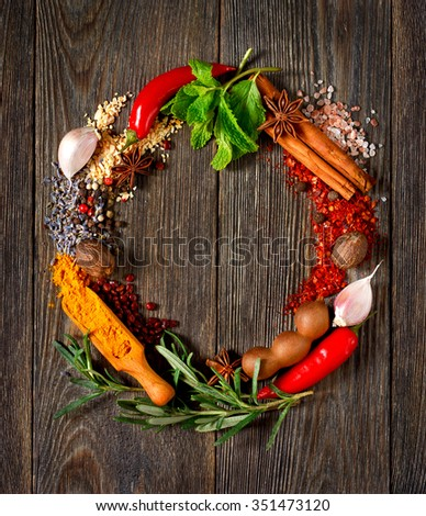 Colorful circle wreath of spices and herbs on wooden table. - stock photo