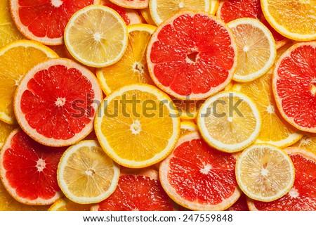 Colorful citrus fruit - lemon, orange, grapefruit - slices background - stock photo