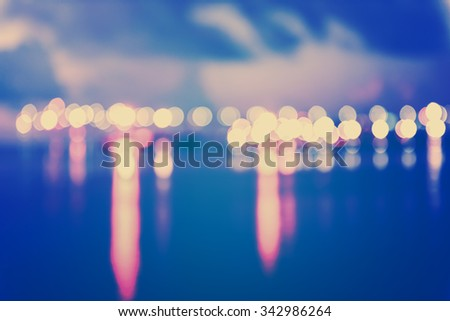 Colorful city lights with bokeh effect reflected over sea background at dusk,retro effect - stock photo
