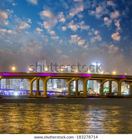Colorful Cityscape of Miami Florida, downtown buildings and MacArthur Causeway bridge illuminating Biscayne bay at sunset - stock photo
