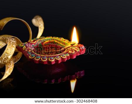 Colorful clay diya lamp with reflection - stock photo