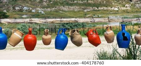 Colorful clay jugs hanging in a line, Cappadocia, Turkey. Vivid jugs, Turkey. Traditional  varicolored jugs. Colorful jugs. Clay jugs, Cappadocia. Row of jugs. Many jugs at sunny day. Cappadocia jugs. - stock photo