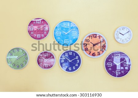 Colorful clocks decorated on the wall, vintage background. - stock photo