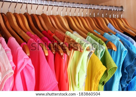 Colorful clothes hanging in wardrobe - stock photo