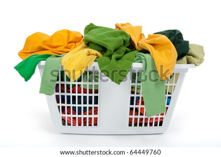 Colorful clothes in a laundry basket on white background. Green, yellow. - stock photo
