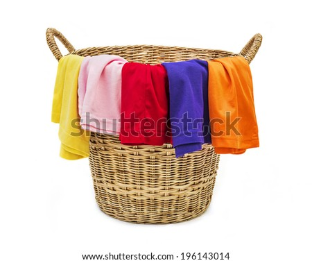 Colorful clothes in a laundry wooden basket on white background