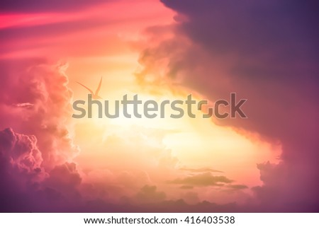Colorful clouds on the dramatic sunset sky, Color toned image,Dramatic sunset sky with colorful clouds and bird. - stock photo