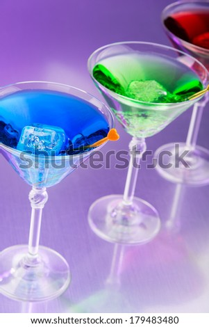 Colorful cocktails in purple light - stock photo