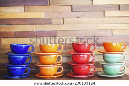 Colorful coffee cups on brick wall background - stock photo