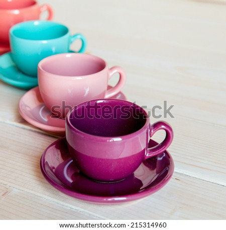 Colorful coffee cups on wooden table - stock photo