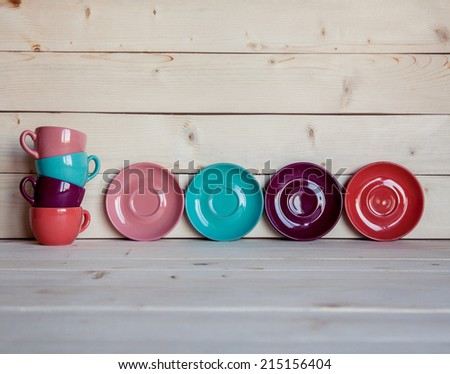 Colorful coffee cups over obsolete grunge wooden background - stock photo
