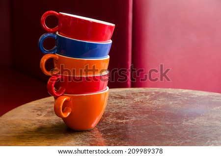 colorful coffee cups stacked on an old wooden table in a cafe  - stock photo