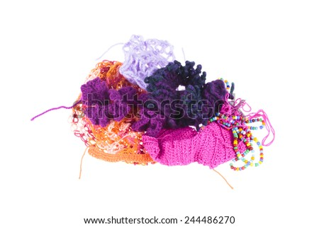 Colorful collection of knitted articles from various colored wool and strings of decorative beads on a white background - stock photo