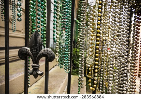 Colorful collections of Mardi Gras bead hanging from a rail with a fleur de lis - stock photo