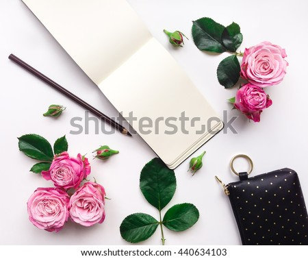 Colorful composition with sketchbook, roses and accessories. Flat lay on white table, top view