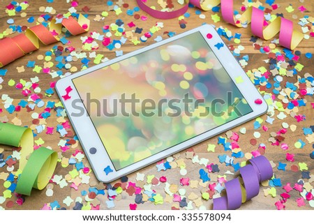 colorful confetti and paper streamers on wooden table with colourful template on tablet - stock photo