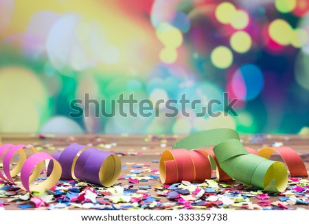 colorful confetti and streamer lying on floor in fron of background - stock photo