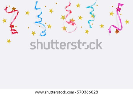 Colorful confetti stars, streamers on a light background. Holiday accessories to decorate the party.