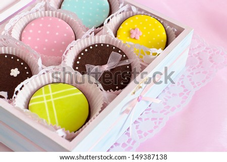 Colorful cookies in wooden box. Decorated with royal icing. Selective focus on brown cookie in the middle. - stock photo