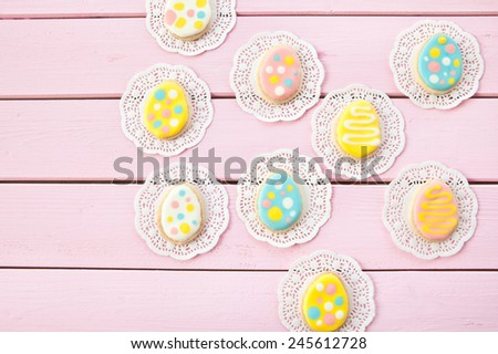 Colorful cookies with polka dots for Easter on pink wooden boards - stock photo