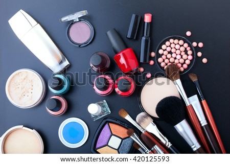 Colorful cosmetics on black wooden workplace. Top view selective focus.