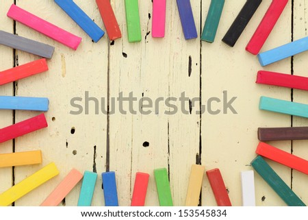 colorful crayons frame on wooden background - stock photo