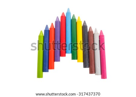 Colorful crayons on white book background - stock photo